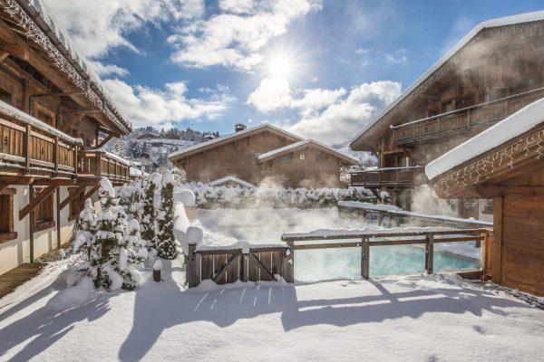 La piscine extérieure chauffée au cœur du hameau des Loges Blanches hôtel **** à Megève