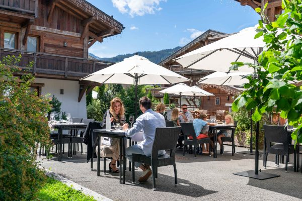La terrasse au milieu du hameau du restaurant La Table des Cochers aux Loges Blanches hôtel 4* à Megève